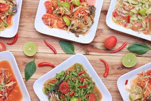 Collection of thai food on wood floor,papaya salad (SOM TUM),Spicy Grilled Pork Salad and Grilled Fish