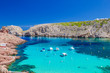 Cala Morell cove with its red rocks and crystal clear blue water