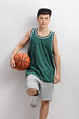Teenager in green jersey holding basketball and leaning on wall