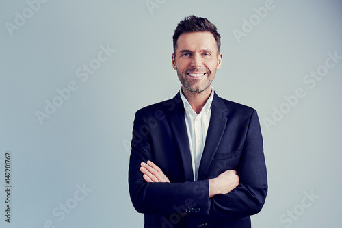 Fototapeta Happy businessman isolated - handsome man standing with crossed arms
