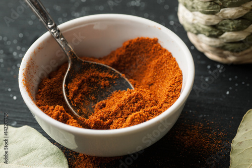 Ground paprika powder in a white ceramic bowl with metal spoon in it, closeup shot