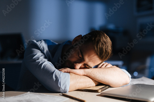 Portrait of exhausted man falling asleep at workplace in dark room late at night, his face lit by lamp light