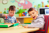 Fototapety cute kids with special needs playing with developing toys while sitting at the desk in daycare center