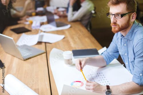 Poster Idea. Designer sitting beside desk in modern studio.