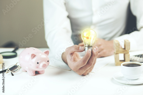 Business Man Hand Light Bulb And Piggy Bank