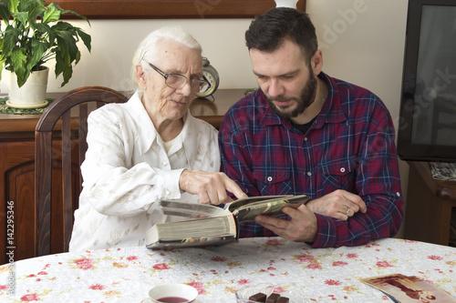 Poster Babcia z wnuczkiem wspominają dawne czasy oglądając album ze zdjęciami