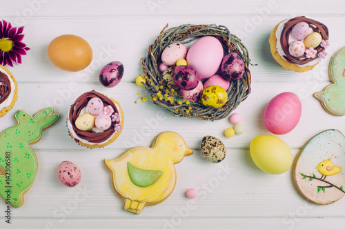 Poster Easter nest cupcakes, painted eggs and ginger breads on light wooden background