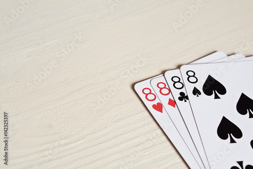four eight poker hands playing cards on a light desk background Poster