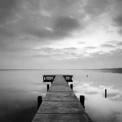 Stiller See mit Steg bei Sonnenaufgang, wolkiger Himmel, schwarz-weiß