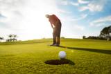 Senior man putting golf ball