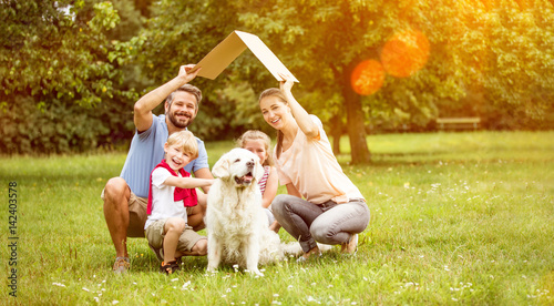 Leinwanddruck Bild Familie mit Dach über Kopf als Symbol für Hausbau