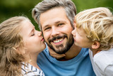 Kinder geben Vater einen Kuss