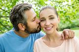 Mann küsst seine Frau liebevoll