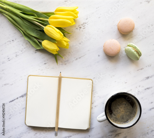 Foto op Canvas Macarons Top view of notebook, coffee, macarons and tulips on marble background