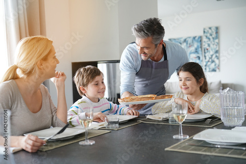 Dad serving pizza to family at dining table - 142431504