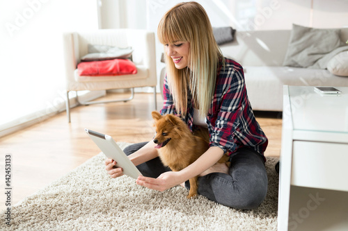 Poster Beautiful young woman with her dog using digital tablet at home.