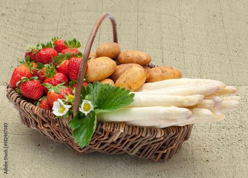Spargel-Erdbeer-Weidenkorb auf Holzuntergrund