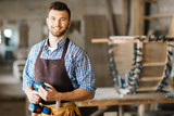 Waist-up portrait of smiling bearded craftsman with electric drill in hands standing in spacious workshop and looking at camera - 142471129