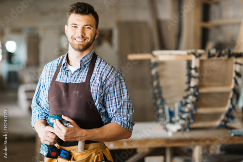 Waist-up portrait of smiling bearded craftsman with electric drill in hands standing in spacious workshop and looking at camera