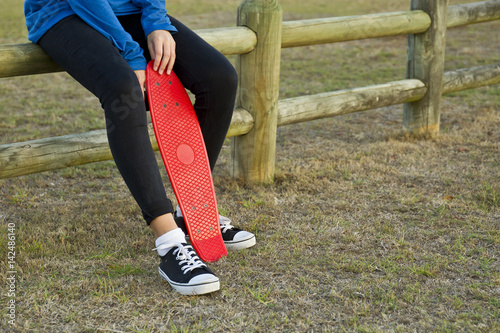 Poster Young woman sitting with her skateboard