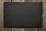 Black slate tile on wooden background . - 142495779