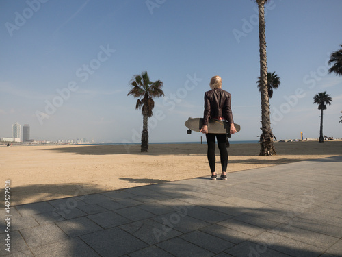 Young modern woman with leather jacket holding a skateboard at the beach in front of a palmtree