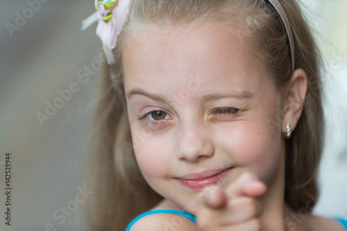 Fotografiet small baby girl with smiling face winking outdoor
