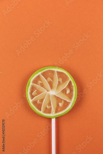 lime lollipop on an orange background Poster