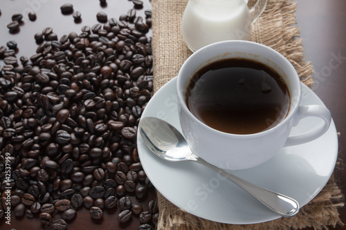 Poster Coffee cup and coffee  beans on table