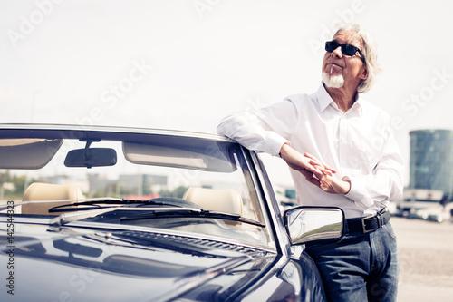 Starszy człowiek stojący obok Cabrio Classic Car