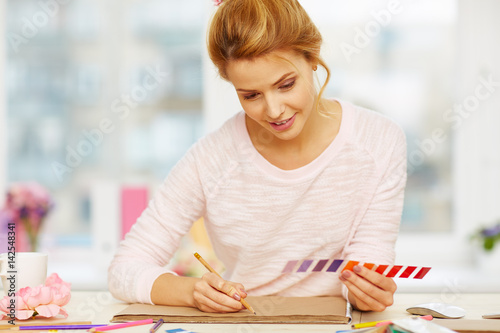 Pretty young interior designer sketching with pencil while holding color swatch  Poster