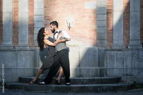 Young couple of sexy beautiful dancers, performing argentine tango dance steps outdoor at sunset, in the old city of Salerno, Italy. Old monumental fountain in the background. Vintage retro look.