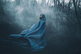 A big, beautiful woman in a blue raincoat, walks in a fog. Background dark forest, bare trees. Creative colors - 142573521