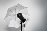 photo studio lightning - strobe flash with white umbrella - 142581366