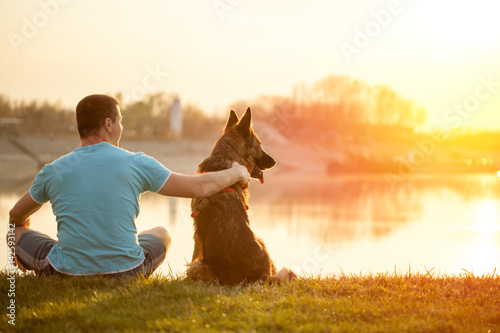 Poster Relaxed man and dog enjoying summer sunset or sunrise