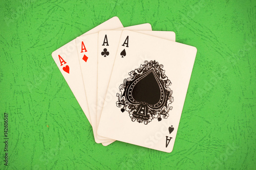 Poster Four aces on a green table. A combination of quads in poker.