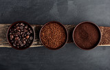 Three kinds of coffee: beans, milled, instant in cups on wooden plank.  - 142616567