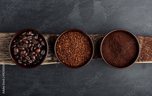 Trzy rodzaje kawy: fasola, mielona, instant w kubkach na drewnianej desce.