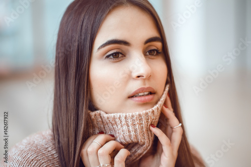 Closeup portrait of pensive white Caucasian European brunette young beautiful woman model with long dark red hair and brown eyes in turtleneck sweater, looking away