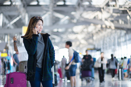 In de dag Charming beautiful business woman smile in casual style using smartphone and hold luggage bag for travel with blur the airport terminal.