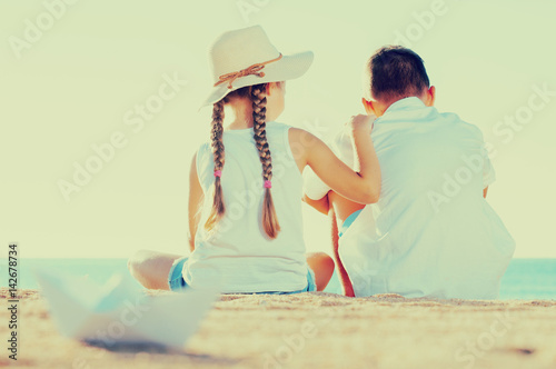 Fotografiet boy and girl sitting beach