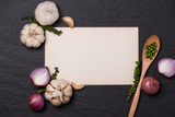 Vegetable recipe. Open menu book with fresh herbs and spices on dark background - 142680147
