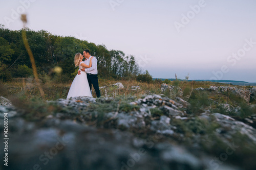 Poster stylish gorgeous couple newlyweds standing on the rocks in the mountains