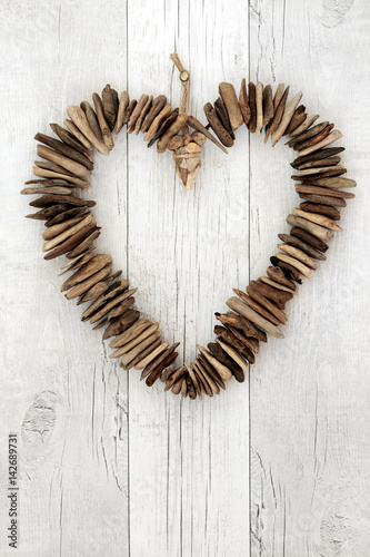 Rustic Driftwood Heart. On distressed white wood background.
