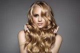 Fototapety Portrait Of A Beautiful Young Blond Woman With Long Wavy Hair