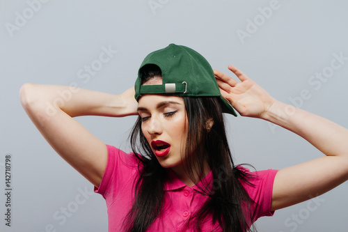 hip hop woman in green cap. Happy, gray background. Poster