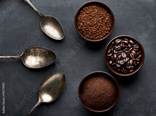 Coffee collection on dark table with vintage spoons.