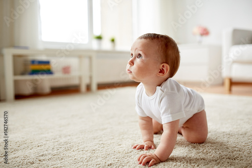 Fotografiet little baby in diaper crawling on floor at home