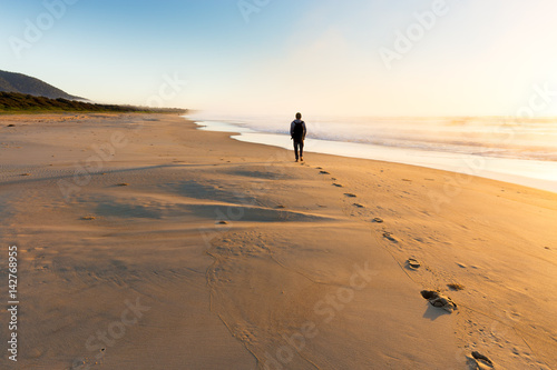 Person Walking Along a Misty Beach at Sunrise