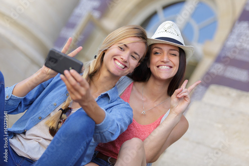 Billede cheerful tourist female friends taking photos of themselves